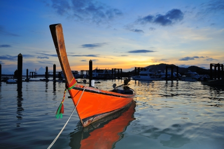 traditional Thai boat in twilight at the chalong Bay of Phuket, Thailand photo