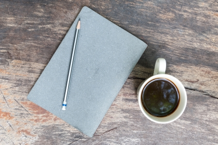 gray note book with coffee cup on grunge wood photo