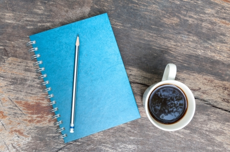 blue note book with coffee cup on grunge wood photo