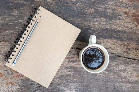 brown note book with coffee cup on grunge wood photo