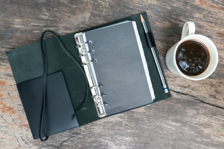 black note book with coffee cup on grunge wood photo