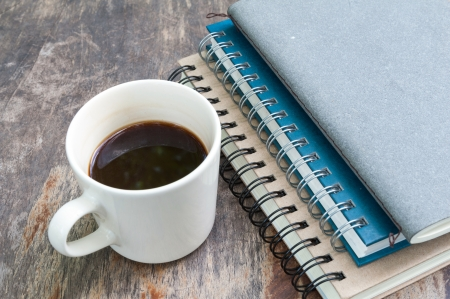various note book with coffee cup on grunge wood photo