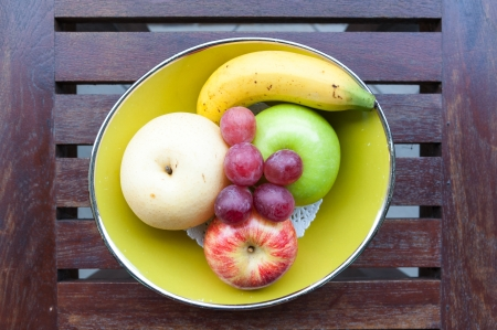 yellow bowl of various fruits on grungy wooden desk photo