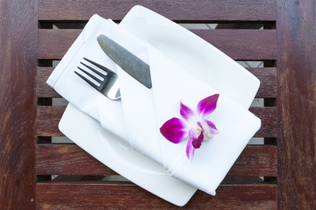 Dinner setting with white orchid on wooden table photo