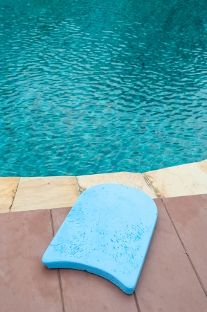 Blue foam board for the teaching of swimming beside swimming pool photo