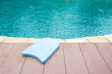 Blue foam board for the teaching of swimming beside swimming pool