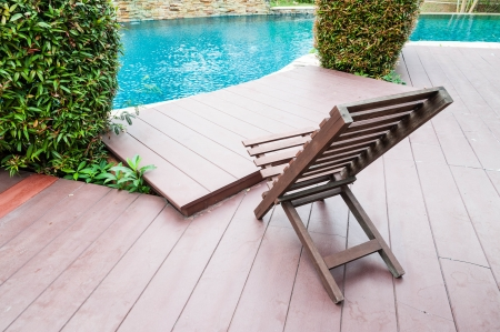 daybed: wooden chair beside swimming pool Editorial