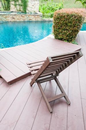 wooden chair beside swimming pool Standard-Bild