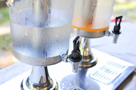 orange juice and water in dispenser Stock Photo