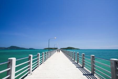 Concrete walk bridge across the sea with the blue sky at rawai beach, phuket Thailand  Stock Photo