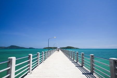 Concrete walk bridge across the sea with the blue sky at rawai beach, phuket Thailand  Stock Photo