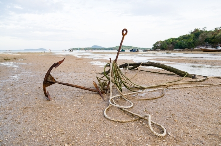 anchoring: Rusty boat anchor on the beach