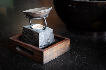 Aroma therapy pot with stone candle base in wooden tray  photo