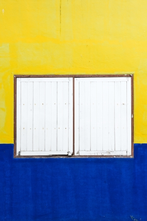 old wooden window on colorful yellow and blue wall  photo
