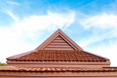 detail of wooden roof gable with clay roof tile on blue sky  photo