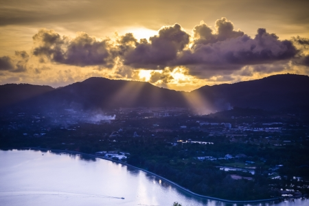 Dramatic sunset on the sea, sun light pass through cloud over mountain, phuket Thailand  photo