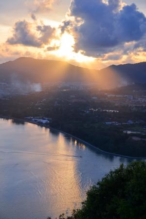 Dramatic sunset on the sea, sun light pass through cloud over mountain, phuket Thailand photo