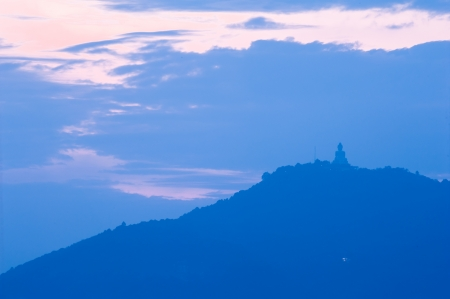 silhouette of big Buddha on the top of mountain in twilight  photo