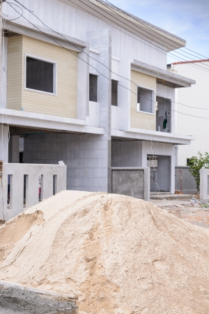 cement pole: Sand pile and building in construction site