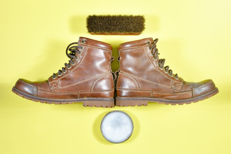 A dirty brown boot with a polish kit Stock Photo