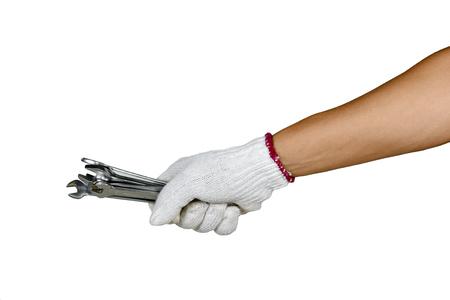una mano con guante de protección sosteniendo varias llaves inglesas sobre fondo blanco