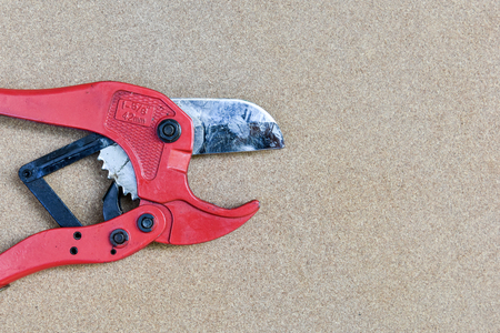 cutter: red scissors for cutting plastic pipe on wooden background with a copy space for text Stock Photo
