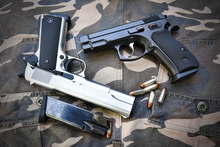 silver: two semi-automatic handguns and bag on camouflage soldier pant Stock Photo