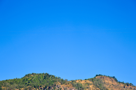 top of mountain with blue sky surrounded by tropical forests of Thailand
