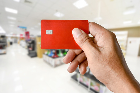 a hand holding credit card blurred electronics store, modern life shopping concept Stock Photo