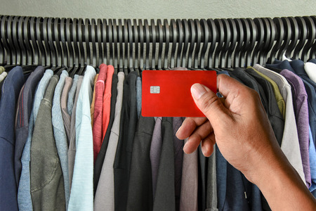 a hand holding credit card on t-shirts rack in shop, modern life shopping concept