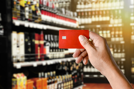 a hand holding credit card on Wine Liquor bottle on shelf, Blurred Supermarket store background, modern life shopping concept