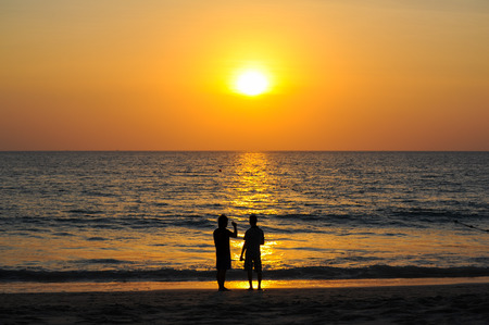 Beautiful Sunset at andaman sea with silhouette people together, Phuket Thailand