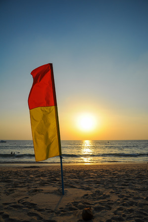 warning flag on the beach in twilight Stock Photo