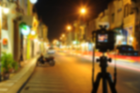 blurred camera on tripod in night street of city background, China town Phuket Thailand