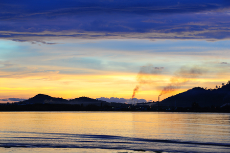 Beautiful sunrise over sea with factory pollution, concept of nature and pollution Stock Photo