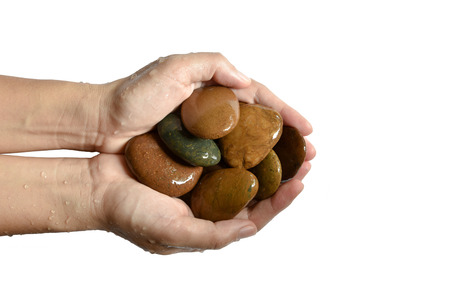 a wet hand holding a pebbles isolated on white background Stock Photo