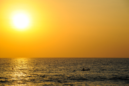 Tiny kayak boat silhouette at sunset, Andaman sea phuket Thailand