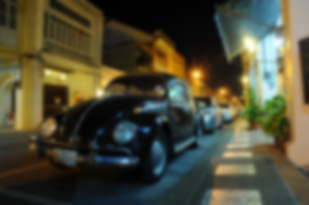 blurred parking car on night street of city background, China town Phuket Thailand