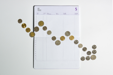 coins array to show graph going down on bank saving account book, risky financial and money savings management concept Stock Photo