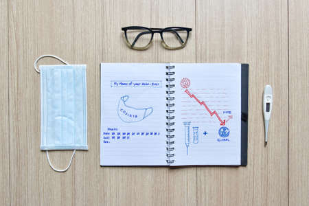 memo of covid 19 passed years diary on wooden floor with mask eyeglasses and thermometer , diaries of covid-19 showing graphic sketch of mask, vaccine and hope, global economy, virus and quarantine