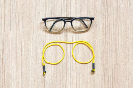 Clear eyeglasses, Glasses transparent dark blue frame with yellow eyeglasses strap on a wooden background