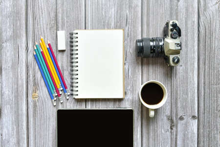 Still life, business or traveler memo concept, Top view image of open notebook with vintage camera coffee colorful pencil and tablet with blank pages on old brown wooden background, for adding text