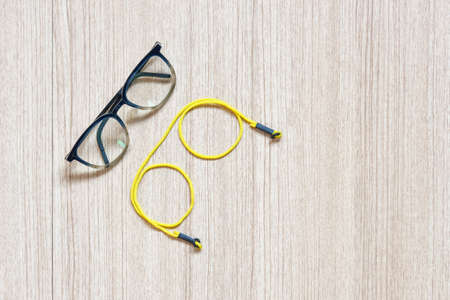 Clear eyeglasses, Glasses transparent dark blue frame with yellow eyeglasses strap on a wooden background, ready to add text for copy space
