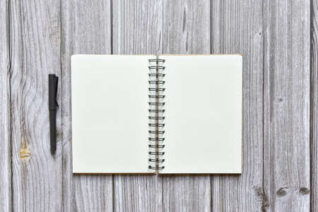 Still life, business office supplies or education concept, Top view image of open notebook and fountain pen with blank pages on old brown wooden background, ready for adding text