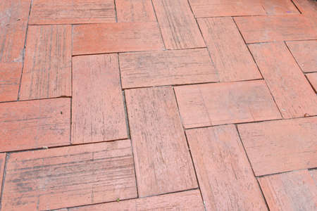 Close-up of an aged brick paved courtyard, a pattern of clay brick lay to for pattern zigzag style, old pavement brick floor also call brick paving