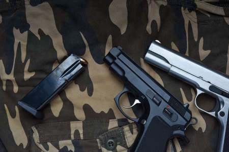 Still life with black and silver handgun with cartridge magazine on camouflage soldier pant background, Black and chrome semi-automatic pistol on camouflage soldier pant