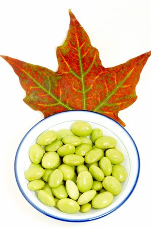 red maple leaf: a dish of green beans with red maple leaf on white background