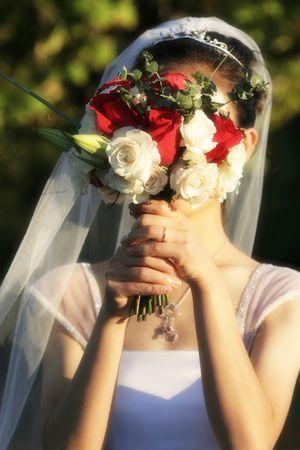 花嫁は彼女の結婚式の日に彼女の顔の前で彼女の花束を保持