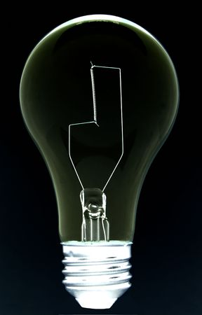 close up of an isolated light bulb against black background with soft bright edge.