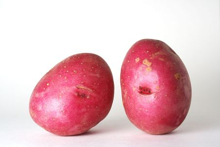 白い背景に、2 つの赤いジャガイモのクローズ アップ。